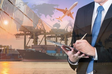 exports: Double exposure of businessman is booking with blurred cargo , transportation port and world map. Transportation logistic business concept. Stock Photo