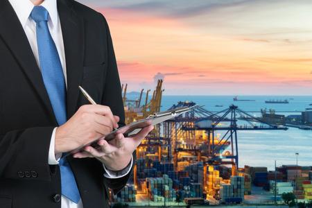 Zakenman schrijven notebook voor de handel en logistiek met vage lading container terminal in de haven op de achtergrond. Handelsafdelingen en logistiek concept. Stockfoto