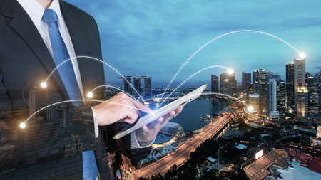 Double exposure of businessman using digital tablet pc with network connection of Singapore city. Network connection concept Foto de archivo