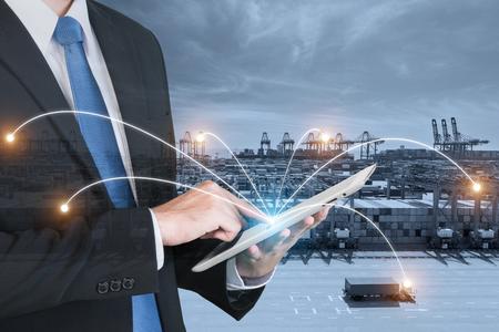 Double exposition de la main d'homme d'affaires tenant l'assistance à la tablette numérique aide à la gestion du système de logistique pour l'importation, l'exportation et la logistique