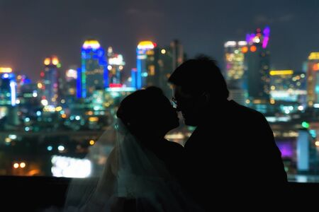 travel woman: silhouette of Asian couple wedding in romance moment on blurred dark night city downtown background. Wedding valentines love story concept.