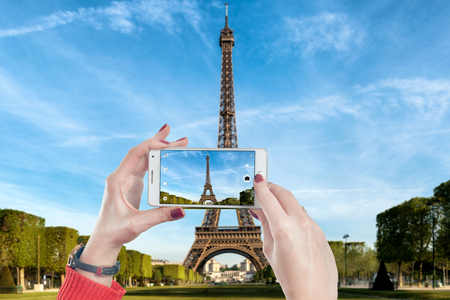 mobile telephone: Shot view of womans hands making photo on mobile phone camera of Eiffel tower in Paris, France. Hipster girl photographing on cell telephone wonderful landmark in Paris, France. Stock Photo
