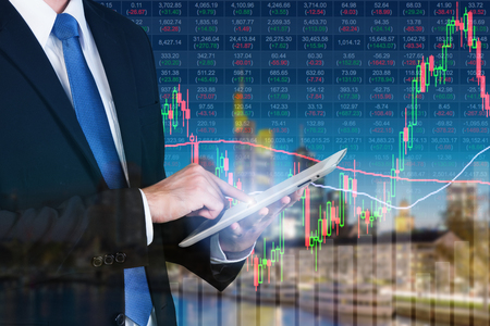 money management: Businessman using digital tablet working with stock market chart in computer screen over the stock market exchange on frankfurt cityscape in background, Business trading and technology concept. Stock Photo