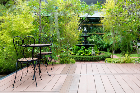 fountain: Black chair in wood patio at green garden with fountain in house. Outdoor garden. Stock Photo