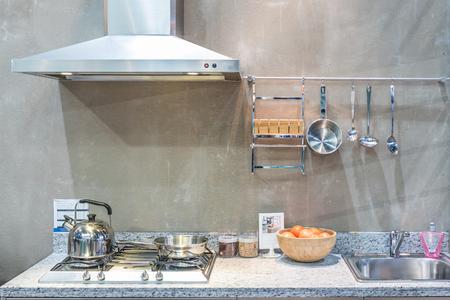 Interior of kitchen with cooker hood, gas stove snd sink at home. Modern appliance kitchen. Standard-Bild