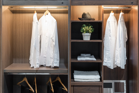 Modern interior wardrobe with shirt, pants, hat and towel in shelf.