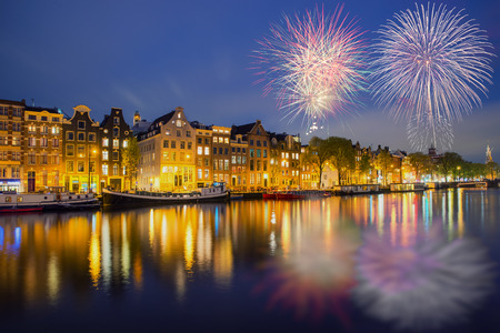 Night Amsterdam city view of Netherlands traditional houses with new year fireworks in Amsterdam, Netherlands