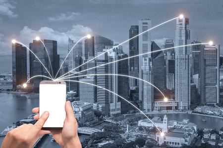 Mano in possesso di smart phone e città di Singapore con connessione di rete. Concetto di connessione di rete smart city.