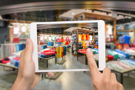 disruption: Augmented reality marketing concept. Hand holding digital tablet smart phone use AR application to check special sale price in retail fashion shop mall Stock Photo