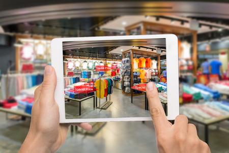 Concept de marketing de réalité augmentée. Hand holding tablette numérique utilisation de téléphone intelligent application AR pour vérifier le prix de vente spécial dans le centre commercial de détail