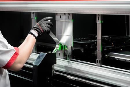 Worker at manufacture workshop operating cidan folding machine Archivio Fotografico