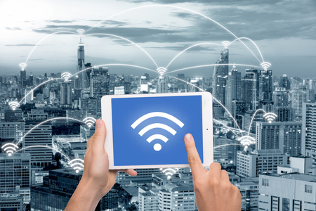 wireless connection: Hand holding tablet with wifi icon on city and network connection concept. Bangkok smart city and wireless communication network, abstract image visual, internet of things.
