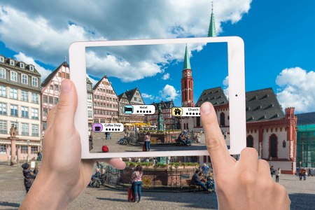 Hand holding smart phone use AR application to check relevant information about the spaces around customer. Frankfurt City in background. Augmented reality marketing concept.