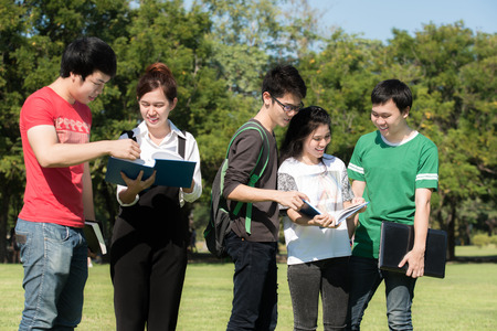 young asian: Group of Asian young attractive smiling students dressed casual standing on park outdoors in campus at the university. University student. Stock Photo
