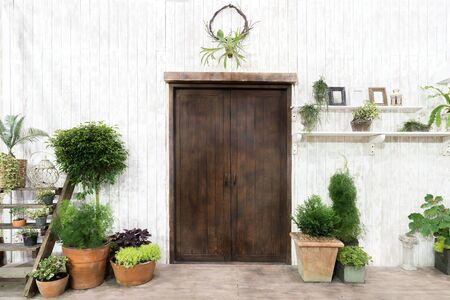 cosy: Front wood door and garden decor in white cosy house or cottage. Exterior of house. Stock Photo