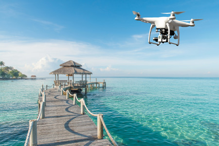 Drone with high resolution digital camera flying over tropical sea in background in Phuket, Thailand. Beautiful landscape Standard-Bild