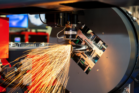 CNC laser cutting metal pipe with bright sparkle in factory. Industry machine. Stockfoto