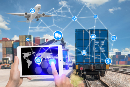 Hand holding tablet is pressing button Logistics connection technology interface global partner connection for logistic import export background. Business logistics concept , internet of things Stockfoto