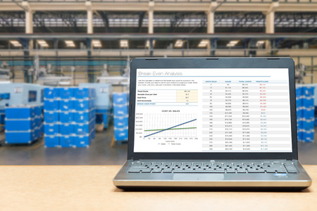 cost: Laptop with analysis screen on table with blur warehouse cargo in factory. Smart factory concept. Stock Photo