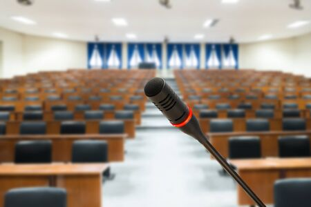 empty room background: Microphone with blurred photo of empty conference hall or seminar room in background. Business meeting concept