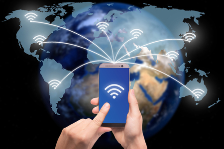 wifi: Hand holding smart phone on world map network and wireless communication network, abstract image visual, internet of things.Elements of this image furnished by NASA