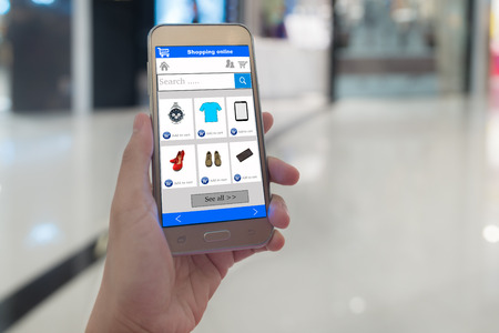 web shopping: Smart phone online shopping in woman hand. Shopping center in background. Buy clothes shoes accessories with e commerce web site Stock Photo