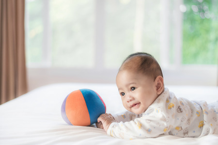 Portrait of 4 month Asian baby lying and playing colorful ball on white bed in bedroom at house.
