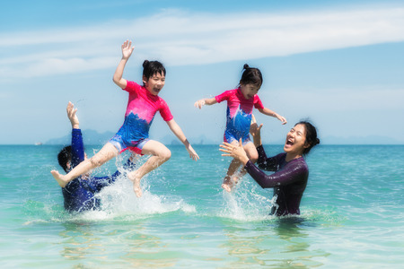 asia children: Happy Asian family playing in the ocean and splashing water in Phuket, Thailand. Asian family tourists on summer vacation on a tropical island.