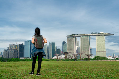 Asian woman solo traveler in Singapore looking at city view with backpack.