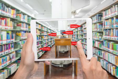 증강 현실 교육 개념. 대학 도서관에서 책장에서 라이브러리 범주를 확인하기 위해 디지털 태블릿, 스마트 폰 사용 AR 응용 프로그램을 들고 손.