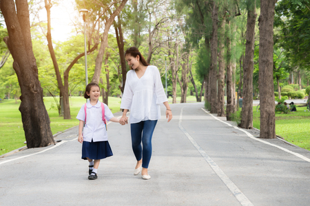 Asian mother and daughter student walking to school.