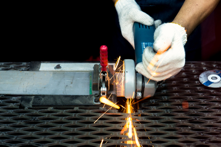 wheel spin: Worker cutting with grinder and welding metal with many sharp sparks in factory Stock Photo