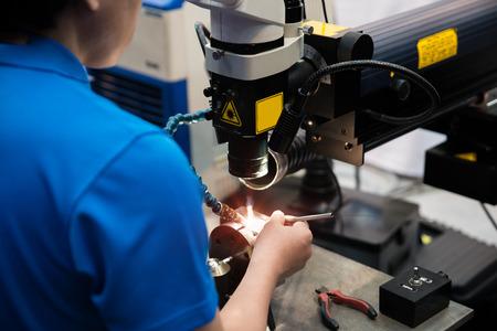 Worker welding repair mold and die part by Laser welding machine in factory.