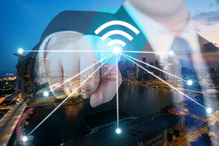 wireless connection: Businessman push wifi icon on city and network connection concept. Singapore smart city and wireless communication network, abstract image visual, internet of things.