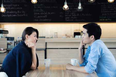 Dating in a cafe. Beautiful Asian lover couple sitting in a cafe enjoying in coffee and conversation. Love and romance.
