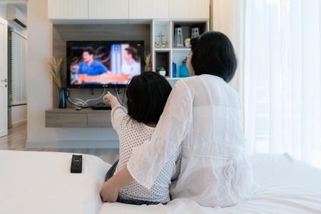 행복 한 아시아 가족 어머니와 딸 집에서 거실에서 평면 스크린 텔레비전을보고 소파에 앉아. 가족 시간.
