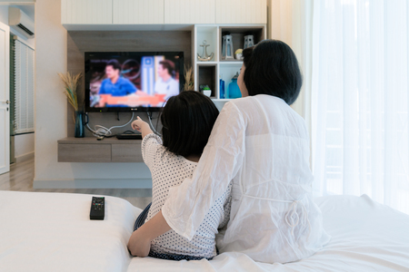 Happy Asian family mother and daughter sitting on sofa watching flat screen television at living room in home. Family time.