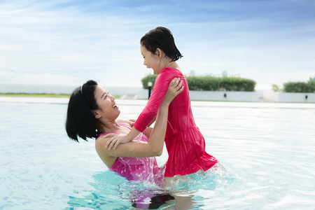 Happy Asian mother raise daughter in hotel swimming pool near sea her child having fun enjoying summer vacation. Asian family concept.
