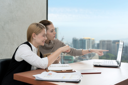 Caucasian business women working together at the office on a laptop computer. Business partnership people concept. Stock Photo