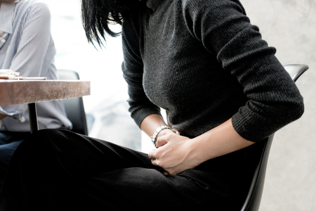 Asian woman has stomachache while she meeting with her friend in cafe. Stockfoto