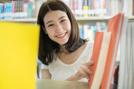 Portrait of an Asian college student seaching book for reseach in library. Stock Photo