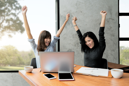 Happy excited successful Asian two business woman making arms up in office. Successful business team.