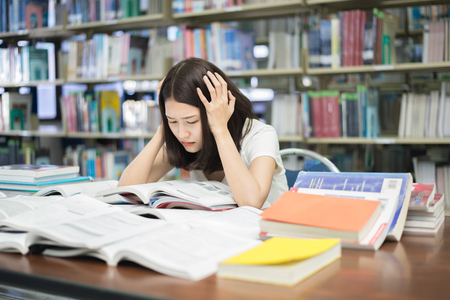 Young Asian student under mental pressure while reading book preparing examination in library at university. Asian student looking stressed.