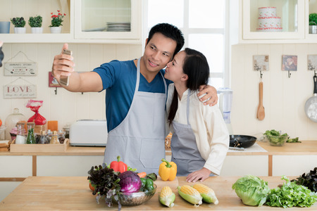 Asian handsome guy is smiling and cooking in kitchen while doing selfie using smartphone at home. Happy love couple concept.