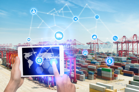 Hand holding tablet is pressing button Logistics connection technology interface global partner connection for logistic import export background. Business logistics concept , internet of things Editorial