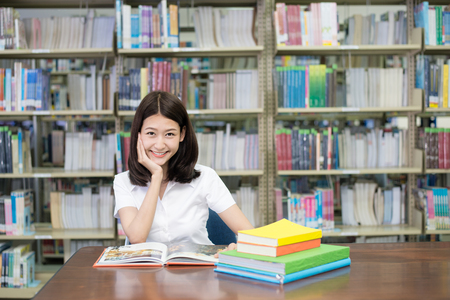Asian student in uniform reading book for learning in library at university. One Asian student. Stock Photo
