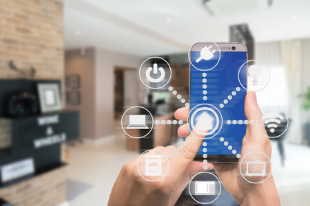 Smart home automation app on mobile with home interior in background. Internet of things concept at home. Smart technology 4.0 Archivio Fotografico