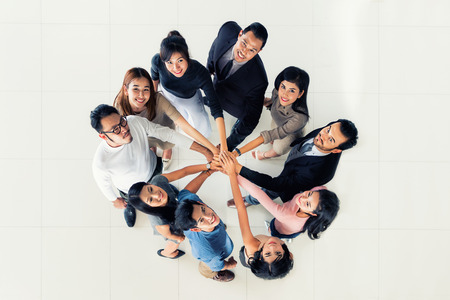 Top view of Group of multi-ethnic business partners putting hands together. Concept of business teamwork and success. Stock Photo