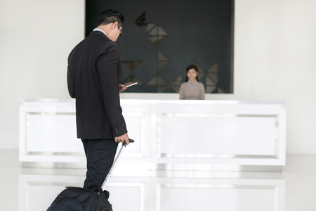 Asian businessman walking to check in at hotel reception front desk.