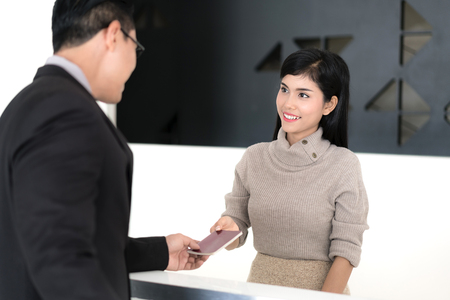 Asian Beautiful girl at the reception of a hotel checking in with businessman.